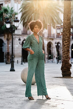 Young African American Female With Curly Hair And Stylish Earrings Wearing Trendy Green Polka Dot Jumpsuit Looking At Camera While Standing Against Blurred Urban Background