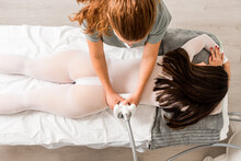 From Above Unrecognizable Masseuse Doing Anti Cellulite Lipo Massage To Female Client Waist Dressed In White Suit During Body Care Procedure In Salon Of Apparatus Cosmetology