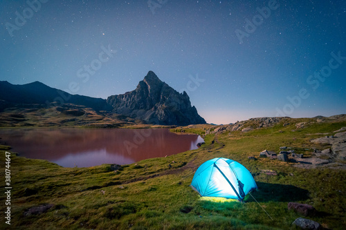 Spectacular view of camping tent placed on meadow near lake in mountainous area under starry sky in long exposure - 380744647
