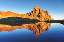 Majestic Scenery Of Calm Water Of Lake On Background Of Mountain Top Lit By Sunlight Under Blue Sky