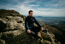 Bearded Male Traveler Sitting Cross Legged On Rock And Meditating With Closed Eyes Against Cloudy Sky In Puerto De La Morcuera Mountains In Spain