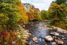 Stunning Autumn Colours Along A Mountain River On A Partly Cloudy Fall Day. Jackson, NH, USA.