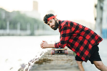Side View Of Male Hipster In Checkered Shirt Leaning On Longboard On Stone Border Of Embankment And Looking At Camera