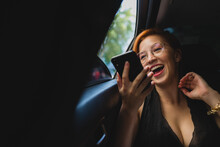 Cheerful Female Entrepreneur Sitting In Luxury Car And Recording Voice Message While Working And Using Cellphone
