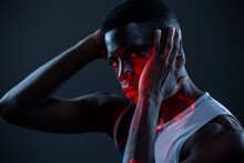 Side View Of Serious Brutal African American Athlete In Sportswear Keeping Hands On Head And Looking At Camera With Challenge While Standing In Dark Studio With Red Neon Lights