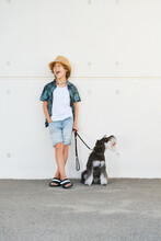 Vertical Photo Of A Child With Curly Hair, Straw Hat And Summer Clothes Leaning Against A Wall With A Dog On A Leash