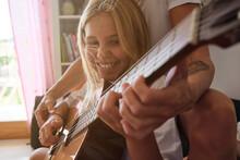 Blonde Girl Playing Guitar Whi...