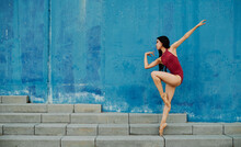 Side View Of Flexible Ballerina In Pointe Shoes And Bodysuit Dancing On Street Near Blue Building While Balancing On Leg