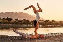 Side View Of Flexible Female Balancing In Handstand Pose On Lying Man While Practicing Acro Yoga Together During Sunset