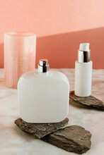 White Cosmetic Spray Bottle And Dispenser For Cream Arranged On Stones On Marble Surface Against Pink Wall