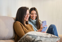 Positive Female Friends Sitting On Couch In Cozy Room And Reading Messages On Social Media On Mobile Phones While Relaxing During Weekend At Home