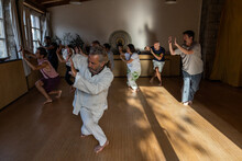 Full Body Of Mature Male Instructor With Group Of Diverse People Performing Chi Kung Pose During Practice In Studio