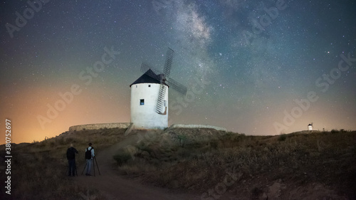Unrecognizable distant photographers with tripod taking pictures of old windmill located on grassy hill against colorful starry night sky