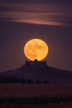 Bright Yellow Moon Glowing On Night Sky Over Distant Castle And Fields In Countryside