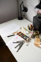 High Angle Of Various Paintbrushes And Watercolor Palette Arranged On Table With Paper And Glass Jar Of Water In Art Studio