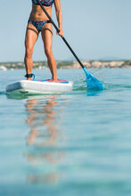 Crop Anonymous Female Surfer Standing On Surfboard And Rowing With Paddle While Practicing On Surface Of Sea In Summer