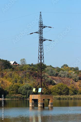 Obraz na plátně Electricity pylon stands in a lake