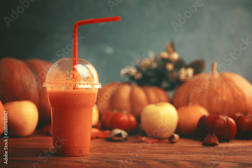 Fototapeta Smoothies in a bottle with a tube on a wooden desk. Carrot juice in bottle with pumpkins. Glass of vegetable juice placed on a table near the pumpkins. Harvest festival, autumn festival.  obraz