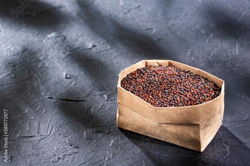 Fototapeta Brassica nigra - Organic black mustard grains in paper bag