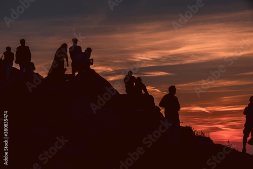 Group of people silhouette admiring a beautiful red and orange sunset in a famous sunset point in Sardinia, Italy Canvas Print