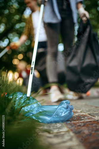 Canvas Print Young volunteers picking trash in plastic bags