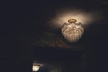 An Old Crystal Chandelier In A Dimply Lit Room
