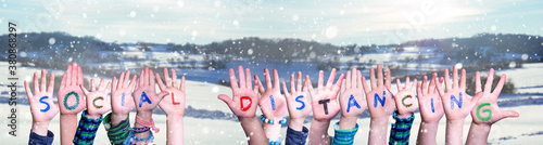 Fototapeta Kids Hands Holding Colorful English Word Social Distancing. Snowy Winter Background With Snowflakes obraz