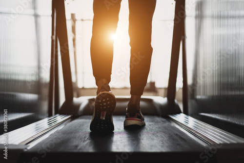 Fotografie, Obraz Young athlete wearing white sport shoes walking on treadmill