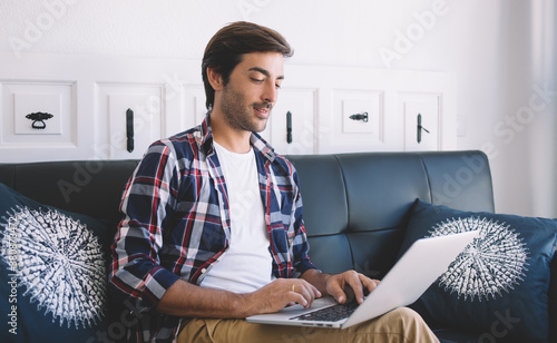 Indian IT professional working remotely with program code for database installation, South Asian man typing text on modern laptop computer using home internet connection for doing distance job