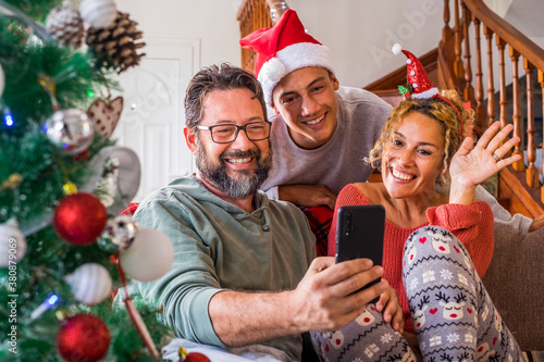 Happy family at home during christmas eve day enjoy a video phone call with friends and parents - concept of happy people and online internet technology - people and modern lifestyle having fun
