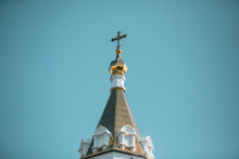 Golden Dome Of The Russian Orthodox Church With The Crucifix Against Blue Sky
