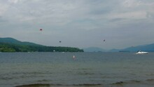 Beautiful Wide View Of Lake George, NY, With Boats Crossing And Parachutes In The Far Background.