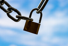 Backlit  Chrome Padlock And Steel Chains Close Up Against Blue Clouded Sky Symbolizing Lockdown