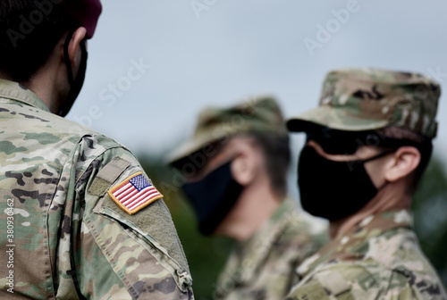 American flag on soldier arm and US soldiers wearing protective face masks. Quarantine in army. Military forces of the United States of America.