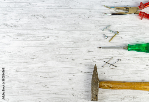 Hand tools on a white wooden background, hammer with nails and a screwdriver wit Canvas Print