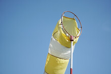 Closeup Of A Yellow And White Windsock Floating In The Air During Daylight