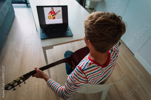 young boy having guitar lesson online at home Fototapeta