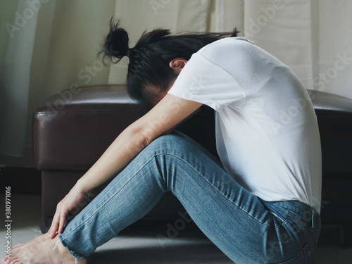 Blurred Young barefoot woman sitting on the floor with her head down and leaning against, sad depressed alone girl Canvas Print