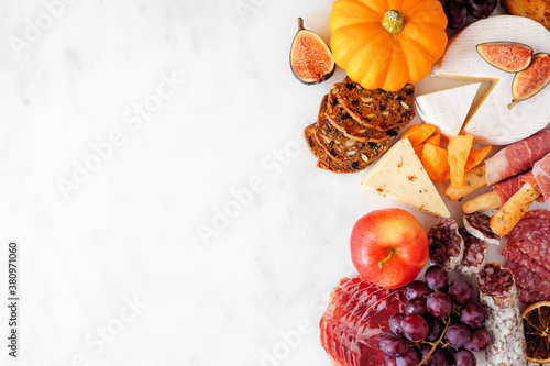Fototapeta Autumn charcuterie side border against a white marble background. Assortment of cheese and meat appetizers. Copy space. obraz