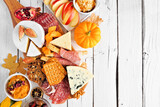 Autumn theme charcuterie side border against a white wood background. Assorted cheese and meat appetizers. Copy space.