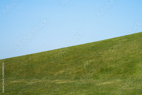 Cuadros en Lienzo a smooth hillside with grass and a blue sky