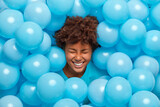 Overjoyed curly haired Afro American woman feels amused and entertained on party has fun and sticks out head through wall decorated with blue balloons expresses happy emotions. Festive event