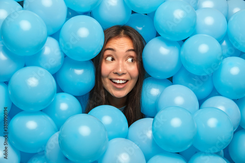 Happy ethnic woman looks mysteriously aside and broad smile poses against blue balloons awaits for special event Wallpaper Mural