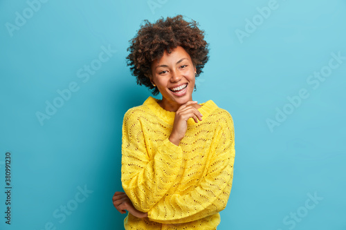 Leinwand Poster Successful happy dark skinned curly woman smiles broadly with white perfect teeth and feels very glad expresses positive emotions dressed in yellow casual jumper isolated on blue background