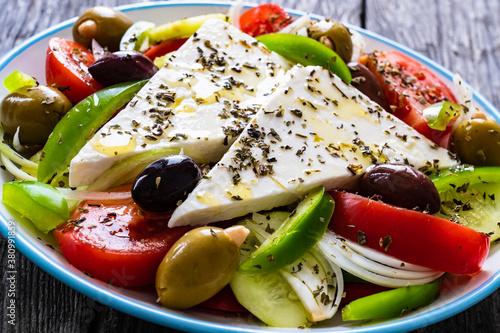 Fototapeta Fresh Greek salad - feta cheese, tomatoes, cucumber, red pepper, black olives and onion on wooden table  obraz