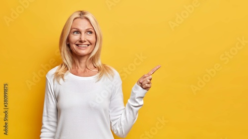 Fototapeta Happy senior woman shows copy space against yellow background smiles pleasantly and has dreamy expression demonstrates vacant advertising spot wears white jumper recommends good offer or discount obraz