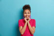 Joyful young Afro American woman keeps hands under chin concentrated above with enjoyment has dreamy expression dressed in casual crimson t shirt isolated on blue background. Human emotions.