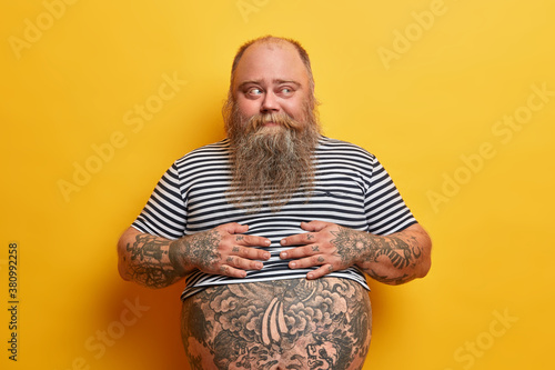 Overweight bearded man with fat belly and tattoos has no sport bad eating habits Canvas Print