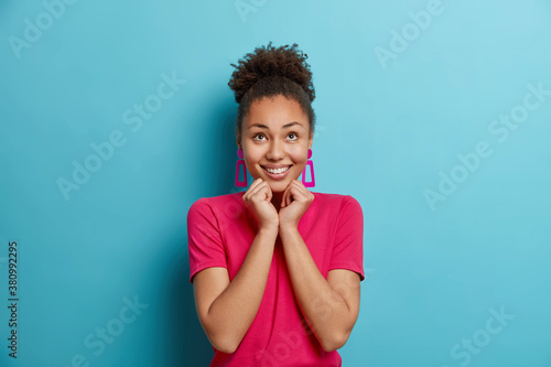 Fotografie, Obraz Joyful young Afro American woman keeps hands under chin concentrated above with enjoyment has dreamy expression dressed in casual crimson t shirt isolated on blue background