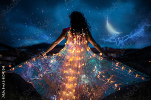 Vászonkép Belly dancer with wings of light under a starry sky